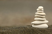 Balancing silky white stones in black grain sand