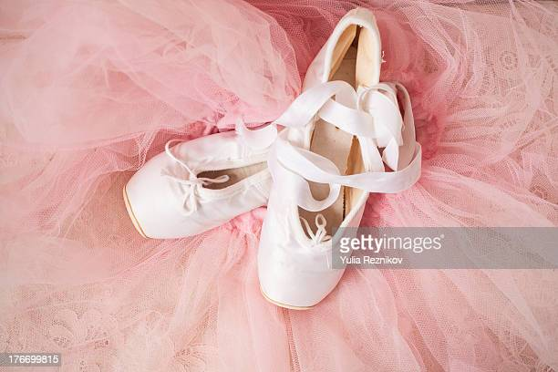 white ballet shoes and pink skirt