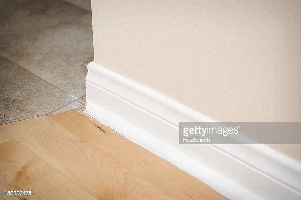 White baseboard along hardwood floor