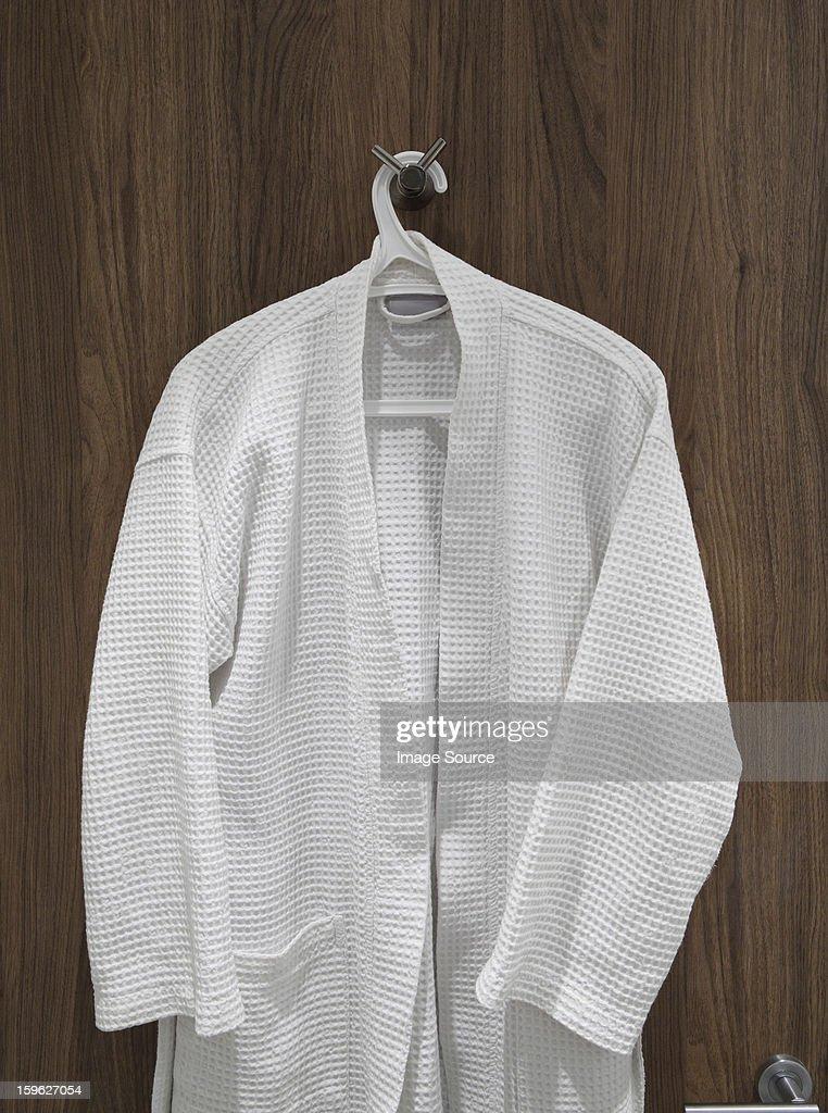 White bathrobe hanging on door