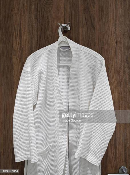 White bathrobe hanging on door