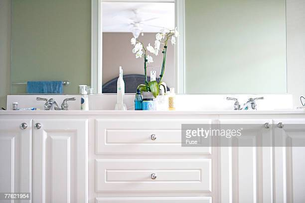 White bathroom counter with two sinks and orchids