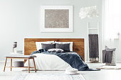 Navy blue blanket on white bed with wooden bedhead and large, silver painting on the wall in bedroom interior