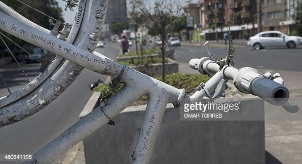 A white bicycle hangs from the structure of traffic signs on March 21 2014 in Mexico City in honor to 23yearold Liliana Castillo who died after being...