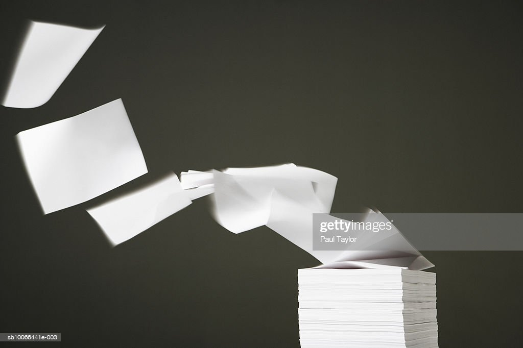 White blank papers blowing off stack, close-up