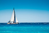 White boat sailing in the open blue sea in Greece