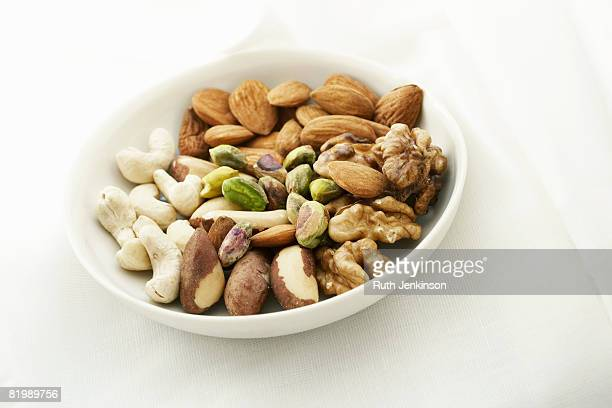 White bowl containing a variety of nuts, close up