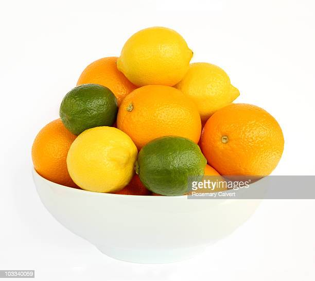 White bowl filled with citrus fruits.