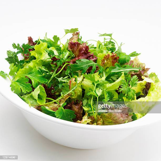 White bowl of mixed herb salad against white