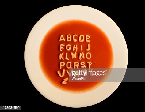 White bowl of soup with alphabet against black background