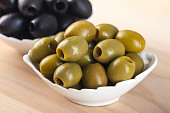 White bowl with green olives on wooden table