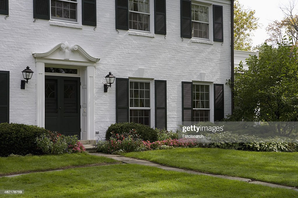 White brick traditional colonial home with black shutters for Brick houses without shutters