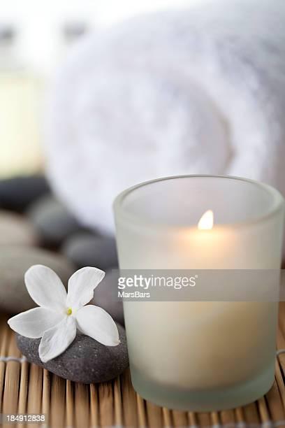 Combustion bougie blanche avec une fleur et une serviette à proximité