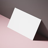 White business card standing near a gray wall on a pink table. Concept of business communication. 3d rendering mock up