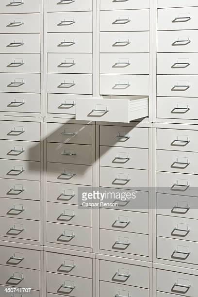 A white cabinet of drawers with one drawer open