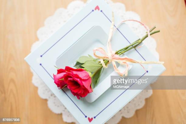 A white cake box with some roses on wooden table