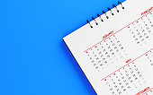 White calendar on blue surface. January, May and February months are visible. Panoramic composition with copy space. Calendar and reminder concept with selective focus.