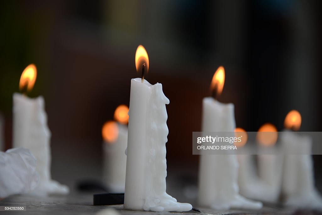 White candles remain lit outside the Public Ministry building in homage to murdered journalists on Journalism Day in Tegucigalpa on May 25, 2016. 63 journalists were murdered in Honduras between 2003 and 2016, according to Human Rights organizations. / AFP / ORLANDO