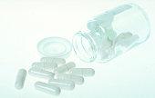 Pharmaceutical white capsules with capsules bottle on blue backgroud.
