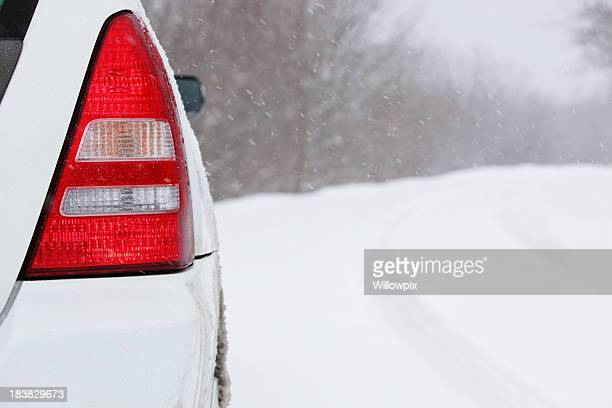 White Car Taillight in Winter Snow Blizzard