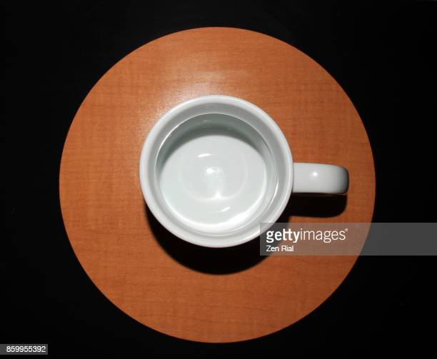 White ceramic cup on brown circular pattern against black background