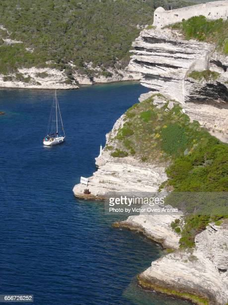 White chalk cliffs of Bonifacio and sail boat entering the harbour in Corsica, France