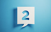 White chat bubble on  blue background. Number two writes on chat bubble. Horizontal composition with copy space.