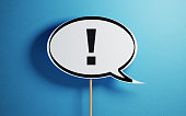 White chat bubble with a wooden stick on  blue background. There is an exclamation point on the chat bubble. Horizontal composition with copy space.