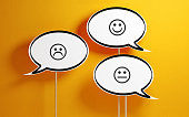 White chat bubble with wooden stick on yellow background. There are various smiley faces on the speech bubbles. Horizontal composition with copy space.