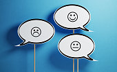 White chat bubble with wooden stick on blue background. There are various smiley faces on the speech bubbles. Horizontal composition with copy space.