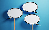 White chat bubbles with wooden sticks on  blue background. Horizontal composition with copy space.