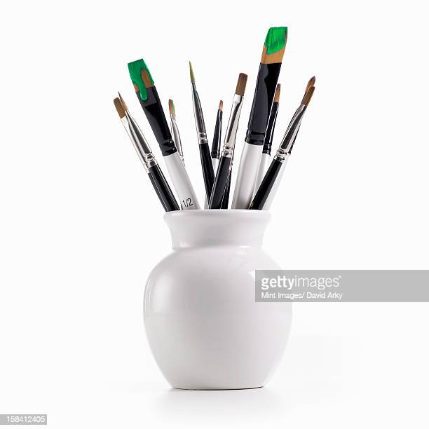 A white china pot full of paintbrushes, some still loaded with green paint.