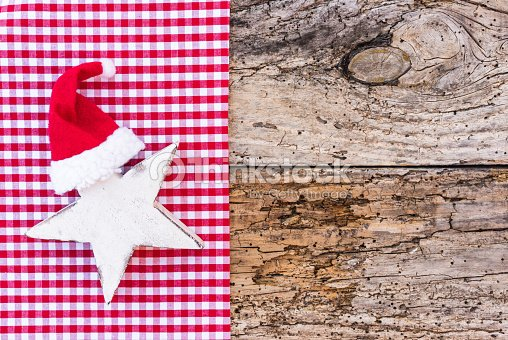 465c8daadb9 White Christmas star shape with red santa hat on rustic wooden background    Stock Photo