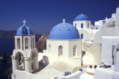 White Church with Belfry and Blue Domes in the Village of Oia Ia on the Santorini Island Greece