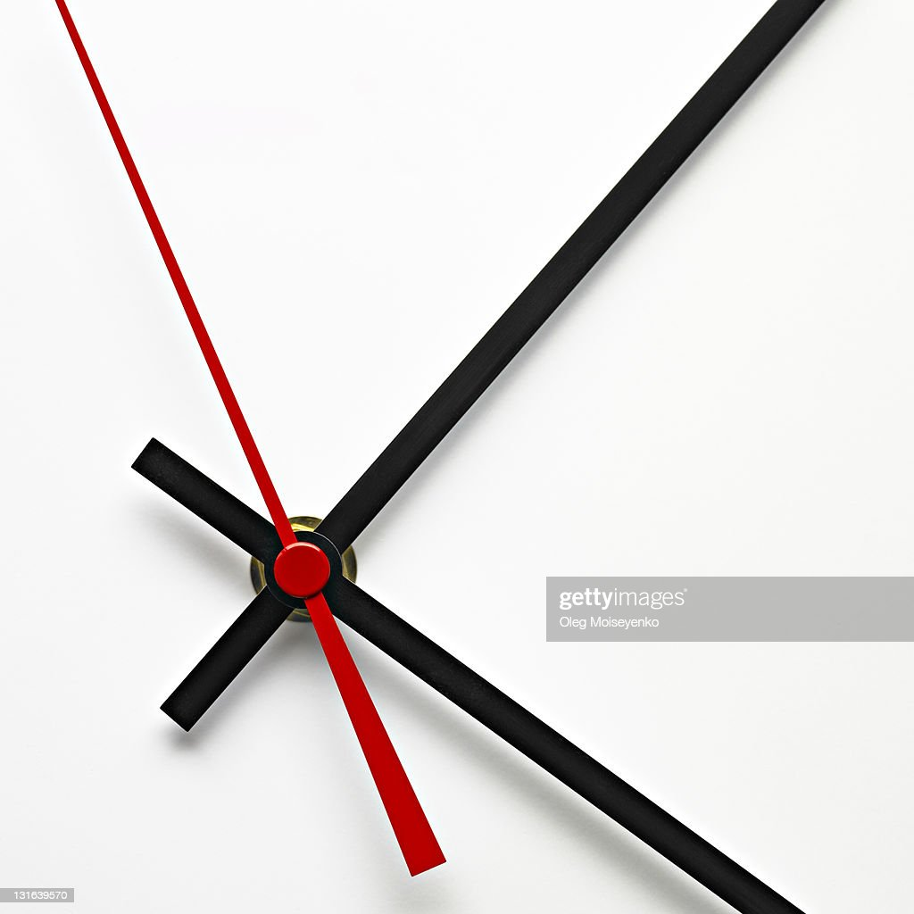 White clock dial with black and red hands