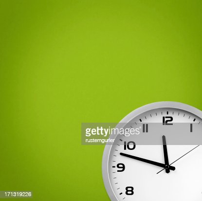 White clock on a green background
