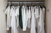 white clothes in cupboard, one green