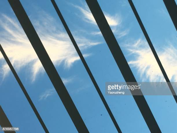White cloud in the shape of feather on bright blue sky. Natural background, cloudy weather.