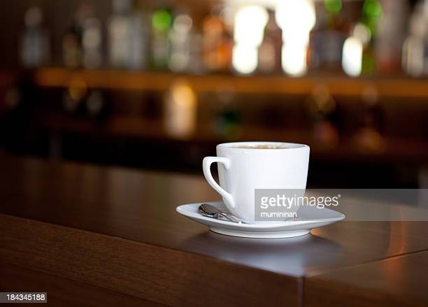 White coffee mug on a wooden bar with defocused background