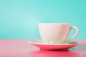 White coffee mug on bright pink and blue background