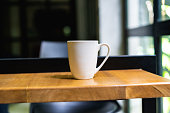 White coffee or tea mug on a wooden table at an office or coworking space