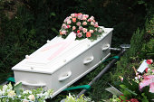 White coffin and several sympathy floral arrangement on a grave side