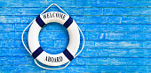 White color Life buoyancy with welcome aboard on it hanging on blue wall. had space on right side for your text.