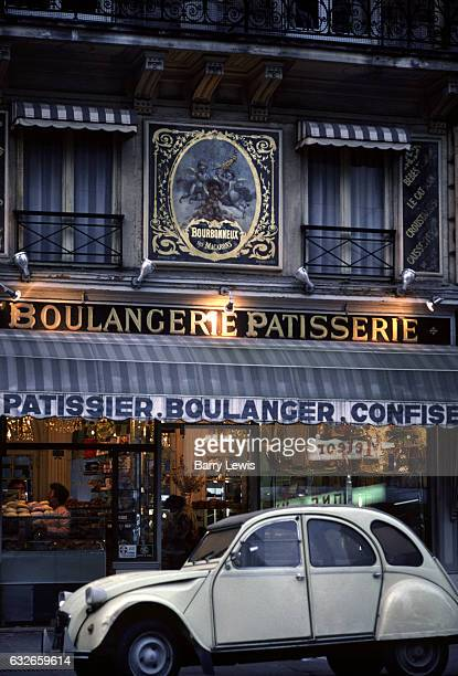A white convertible 2CV car is parked outside a boulanger and patisserie 10th May 1980 Paris France