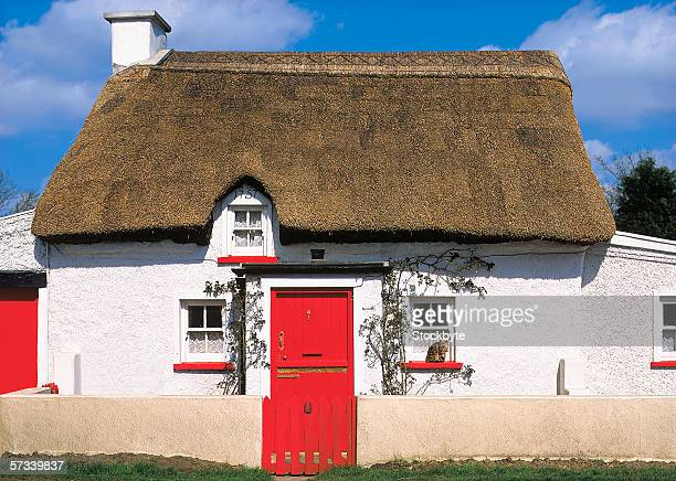 white cottage with thatched roof and a red door
