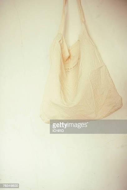 White cotton bag hanging on white wall