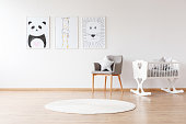 Grey chair with pillow and white round carpet near white crib in baby's room with animal posters on wall