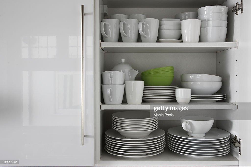 Blanco vajilla apilar en armario con verde bowl : Foto de stock