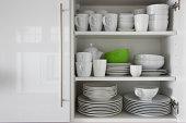 white Geschirr liegen im Schrank mit grünen bowl