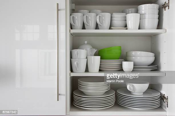white crockery stacked in cupboard with green bowl